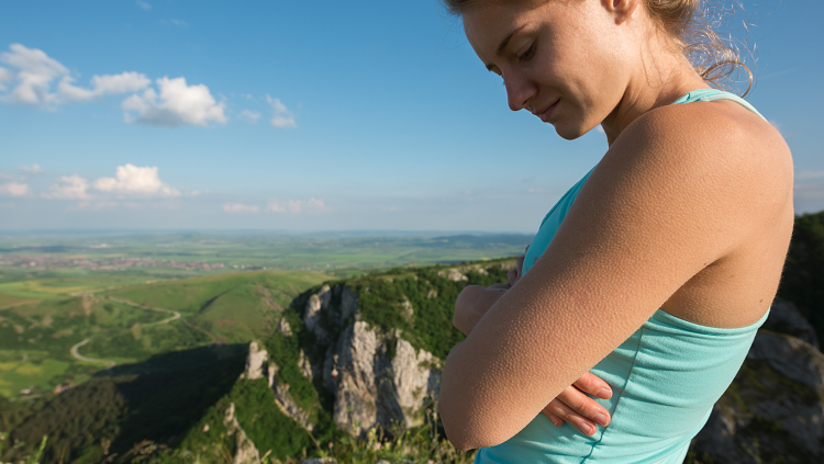 woman with goosebumps looking out on a cliff