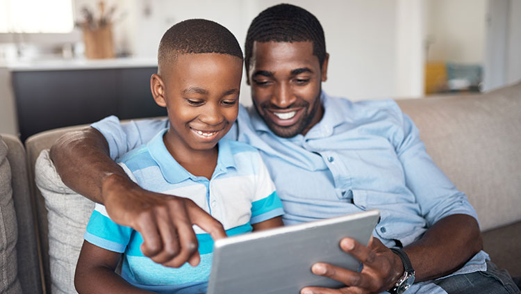 father and son looking at ipad