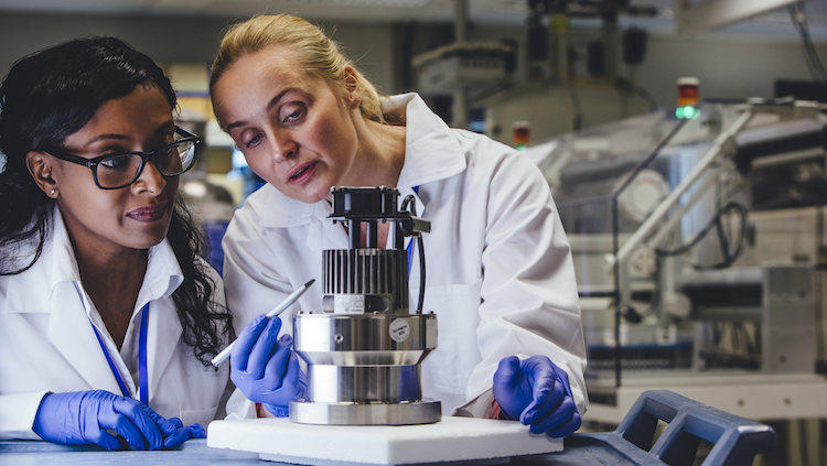 Photograph of two female scientists in lab coats looking at an experiment