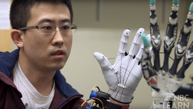 Man holds his hand next to a robotic prosthetic hand.