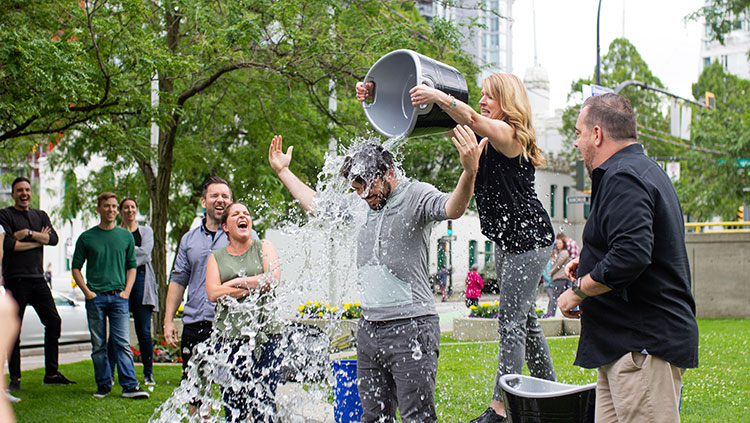 Woman dumping water on man