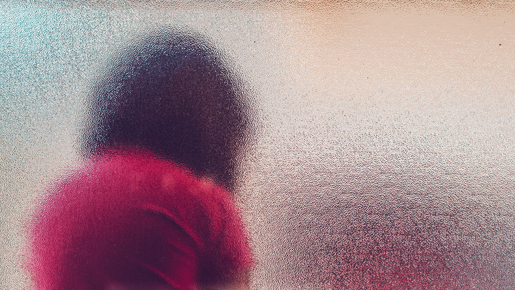person in red shirt leaning their back against a glass wall