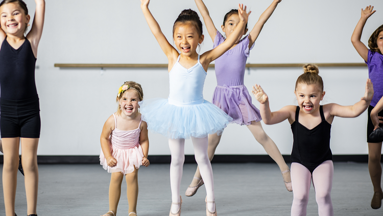 Six young girls in ballet clothes dancing and jumping