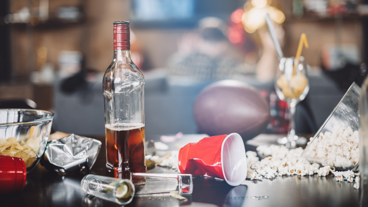 empty cups and liquor bottles on a table