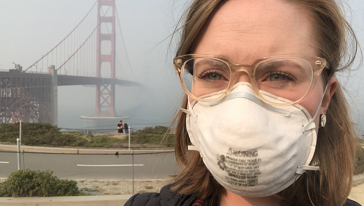 Photograph of woman with mask on in front of Golden Gate Bridge